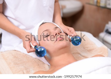 young woman getting facial massage in the spa