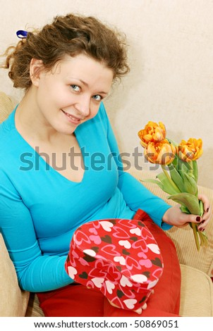 young woman getting flowers and gift - stock photo