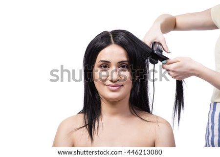 Young woman getting hair straightner isolated on white - stock photo