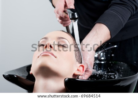 Young woman getting her hair washed at the hairdresser. Close up. - stock photo