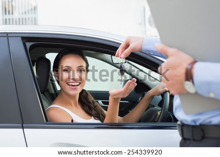 Young woman getting her key in the car - stock photo