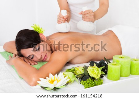 Young Woman Getting Herbal Ball Massage Treatments In Spa - stock photo