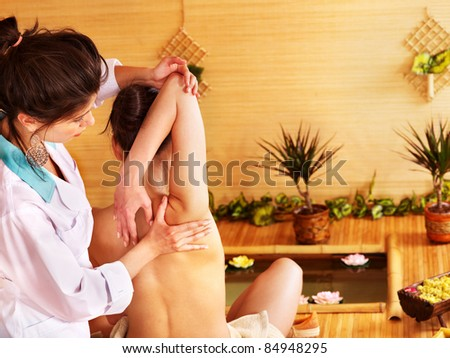 Young woman getting massage in bamboo spa.. - stock photo