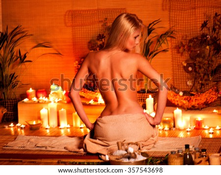 Young woman getting massage in bamboo spa. Back view. - stock photo