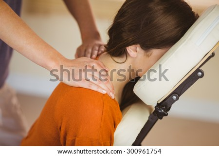 Young woman getting massage in chair in therapy room - stock photo