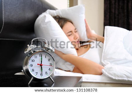 Young woman getting stressed about waking up too early - stock photo