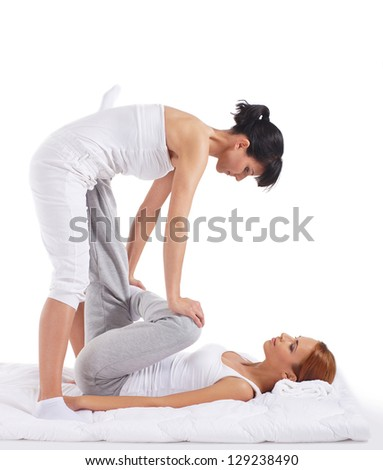 Young woman getting traditional thai stretching massage by therapist isolated on white background - stock photo