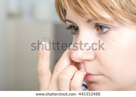 Young woman/girl putting contact lens in her eye close up with copy space . Selective Focus. - stock photo