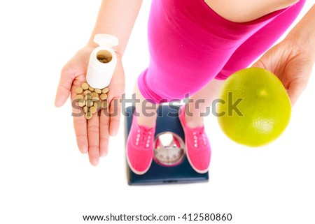 Young woman girl standing on weighing scale holding pills and grapefruit. Choice between synthetic vitamins natural. Health care. Healthy lifestyle nutrition concept. Isolated on white background. - stock photo