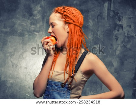 Young woman girl with dreadlocks red hair and apple teenager attractive grunge hipster stile - stock photo