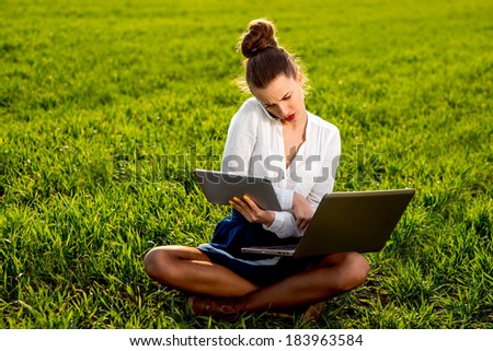 Young woman, girl working with laptop, tablet and phone in green field, park with sunshine - stock photo