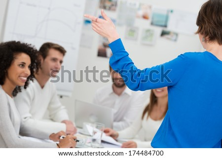 Young woman giving a group presentation standing with her back to the camera talking to her colleagues - stock photo