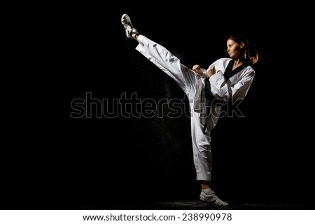 Young woman giving a kick on black background - stock photo