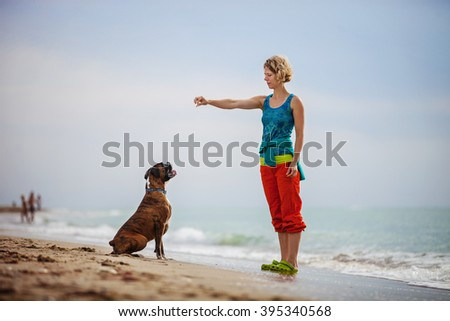 Young woman giving commands to boxer dog while walking on beach - stock photo