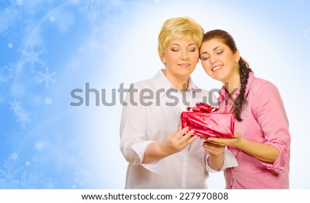 Young woman giving gift to her mother on winter background - stock photo
