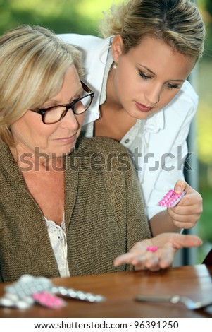 Young woman giving her grandmother medicine - stock photo