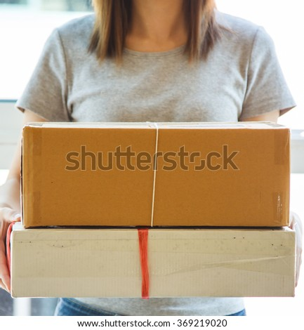 Young woman giving package and delivery concept - stock photo