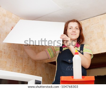 Young woman glues ceiling tile at home