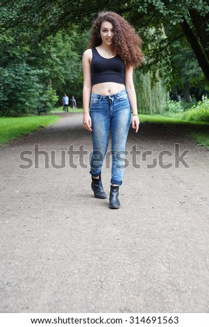 young woman going for a walk in a park with copy space