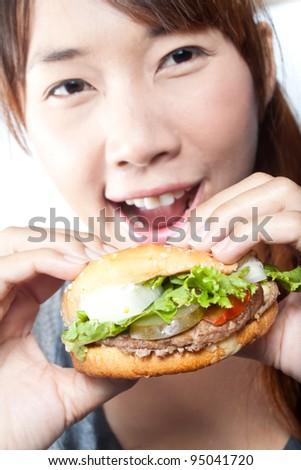 Young woman going to eat burger, shallow  depth of field,  focus at a burger