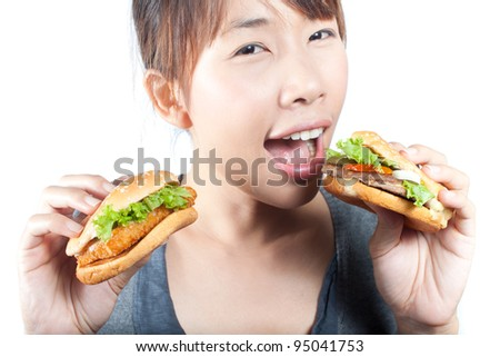 Young woman going to eat two burgers  in her hand on white background
