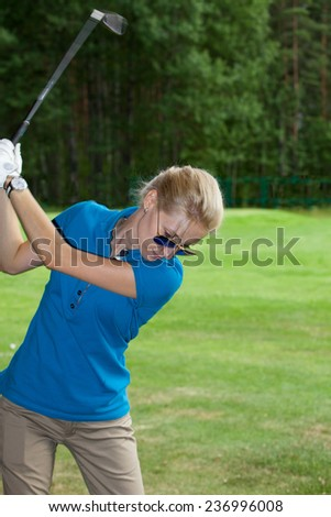 Young woman golf player on course doing golf swing,