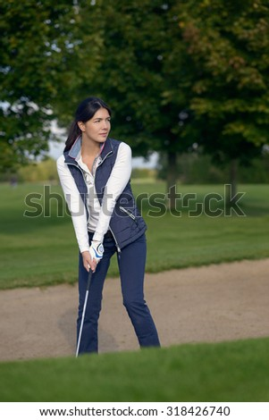 Young woman golfer standing in a sand bunker on a golf course with a club in her hand lining up her shot as she tries to exit the sand - stock photo