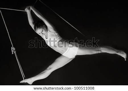 Young woman gymnast on black background - stock photo