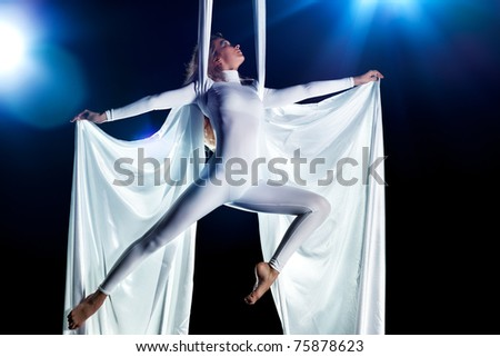 Young woman gymnast. On black background with flash effect. - stock photo