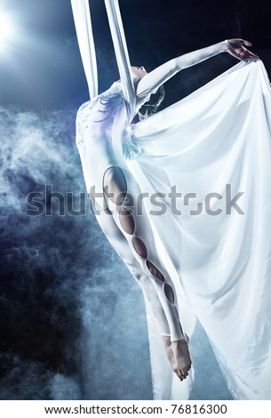 Young woman gymnast. On black background with smoke. - stock photo