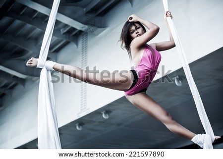 Young woman gymnast. On industrial background. - stock photo