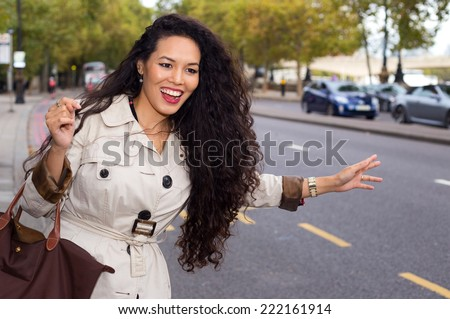 young woman hailing a cab - stock photo