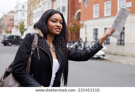 young woman hailing a taxi. - stock photo