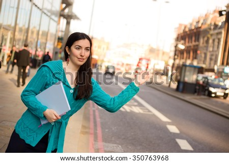 young woman hailing a taxi in the street - stock photo