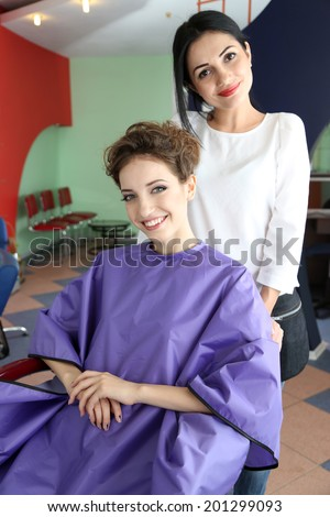 Young woman hairdresser and client in beauty salon