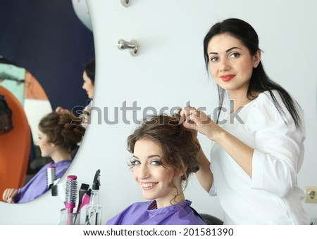 Young woman hairdresser do hairstyle girl in beauty salon - stock photo