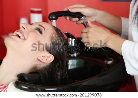 Young woman hairdresser washing girl hair in beauty salon - stock photo