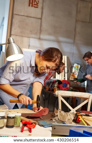 Young woman hammering in workshop, busy.