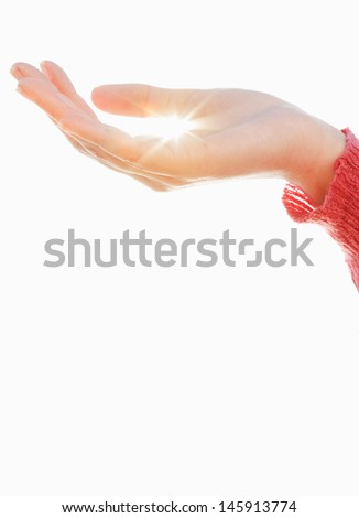 Young woman hand holding the sun against the sky, protecting energy resources and the environment. - stock photo
