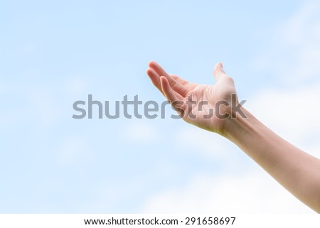 Young woman hand on blue sky white cloud background