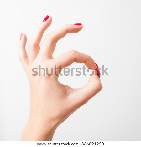Young woman hand with red nails making gesture shows everything is ok on white background - stock photo