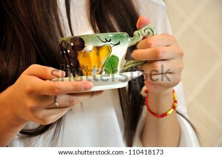 Young woman hands and tea cup