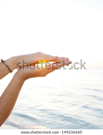 Young woman hands holding and protecting the setting sun in the sky between her hands, filtering rays flare and caring for natural resources.