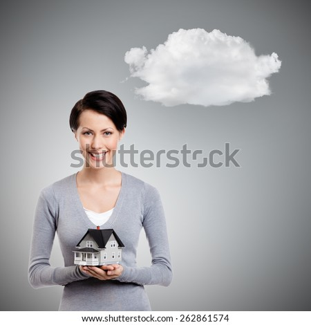 Young woman hands small toy house in front of herself, isolated on grey background with cloud - stock photo