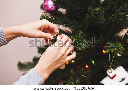 Young woman hands with marriage ring on finger in grey sweater holding a toy decorating christmas tree with copy space on background - stock photo