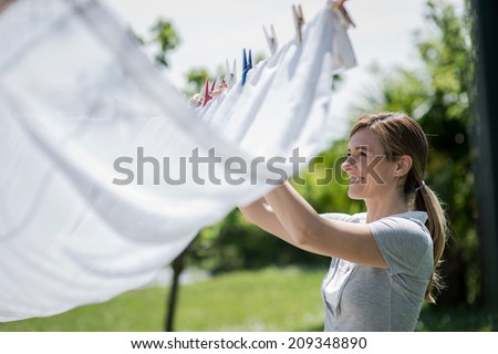 Young woman hanging up laundry - stock photo