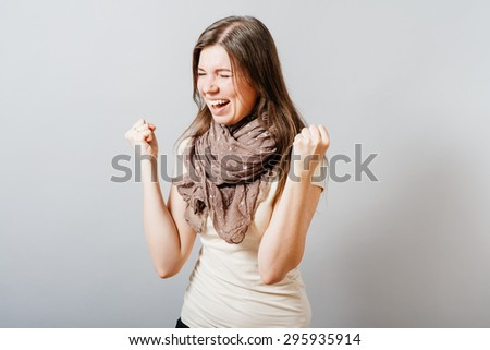 Young woman happily raised her fists up. On a gray background. - stock photo