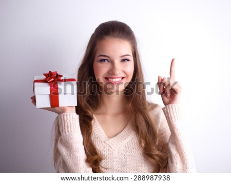 Young woman happy smile hold gift box in hands, isolated over gray background . - stock photo