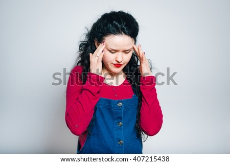 young woman has a headache, dressed in a overalls, close-up isolated on a gray background - stock photo