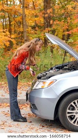 Young woman has a problem with her car on the road - stock photo